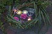 Zink-Wanne mit schwimmenden Lichtern und Blüten
