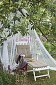 Liege mit Moskitonetz auf der Wiese unterm Apfelbaum