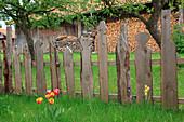 Selbstgebauter Zaun aus künstlerisch gestalteten Brettern