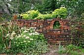 Mauer aus alten Klinkersteinen mit Loch als Durchblick