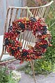 Kränzchen aus Beeren und Herbstlaub an Stuhllehne : Aronia (Apfelbeere)