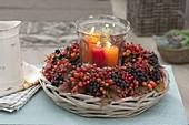 Kränzchen aus Beeren und Herbstlaub auf Korbschale