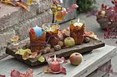 Kleine Windlichter mit Blättern umwickelt, Äpfel (Malus) und Walnuessen