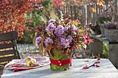 Laendlicher Herbststrauss aus Rosa (Hagebutten), Aster (Herbstastern)