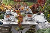 Herbstliche Tischdeko mit Girlande aus Herbstlaub und Hagebutten