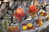 Herbstliche Kerzendeko mit Blättern, Rosa (Hagebutten) und Chaenomeles