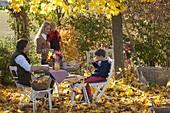 Familie am Tisch im goldenen Herbstlaub unter Ahornbaum