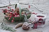 Grüner Korb mit Zapfen, Ilex (Roter Winterbeere) und Pinus (Kiefer)