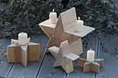 Selbstgemachte Holzsterne mit weissen Kerzen