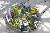 Essbare Blüten im Uhrzeigersinn beginnend bei 12.00 Uhr:\nVergißmeinnicht, Hornveilchen, Löwenzahn, Gänseblümchen, Gundermann, Beinwell, rosa Taubnessel, Knoblauchsrauke, Lungenkraut, Ehrenpreis, Goldnessel, Veilchen, Tausendschön, Ackertäschel und Schlüsselblume