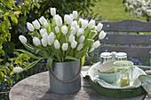Strauss aus Tulipa 'Calgary' (Tulpen) in Zink-Eimer auf Gartentisch