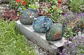 Keramik - Pfaue auf Holzbalken am Beetrand