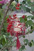 Einmachglas mit Makramee als Windlicht an Baum