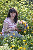 Frau pflückt Strauss aus allem was im Bauerngarten blüht