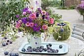 Rosa - Violetter Duftstrauss und frisch gepflueckte Zwetschgen