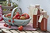 Spankorb mit frisch geernteten Tomaten (Lycopersicon) und Flaschen mit Sugo