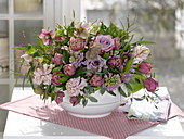 Violet-rosa Fruehlingsgesteck mit Steckhilfe in Suppenterrine