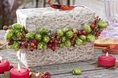 Girlande aus Humulus lupulus (Hopfen) und Rosa (Hagebutten) um Geschenk