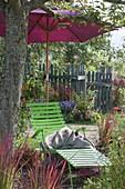 Grüne Liege mit Sonnenschirm unterm Apfelbaum