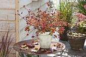 Strauss aus verschiedenen Rosa (Hagebutten) und Herbstlaub auf Rost-Tisch