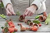 Girlande aus Tontoepfen und Fruchtstaenden als Tischdeko