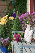 Kleine Sitzecke mit Holzbank am Haus, dahinter diverse Blühpflanzen