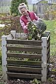 Frau schüttet Gartenabfälle in den Kompost-Behälter