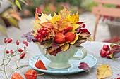 Kleiner Herbststrauss in Tasse auf Untersetzer