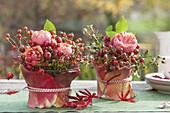 Kleine Sträusse aus Rosa (Rosen, Hagebutten) in Gläsern