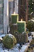 Grüne Kerzen auf Stammstuecken, Mooskugeln, Schlehen , Schnee