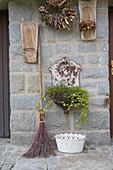 Nostalgisches Arrangement : altes Metall-Waschbecken bepflanzt mit Hedera (Efeu) und Muehlenbeckia (Drahtwein), Reisigbesen, Dachziegel als Wandhalter, Kranz aus Rindenstuecken