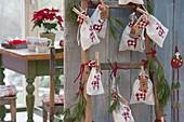 Leiter mit nummerierten Säckchen als Adventskalender , Zweige von Pinus