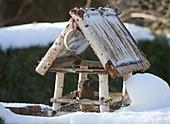 Vogelfutterhaus im Schnee mit Amsel (Turdus merula) , Meisenknödel