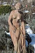 Frauen-Figur aus Terracotta im winterlichen Garten