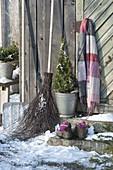 Stillleben am Geräteschuppen mit Schneeschaufel, Reisigbesen, Picea