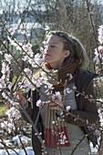 Frau schnuppert an Mandelblüten