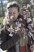 Frau schnuppert an bluehendem Zweig von Viburnum bodnantense 'Dawn'