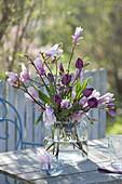 Lockerer Strauss aus Zweigen von Magnolia (Magnolie) und Tulipa 'Negrita'