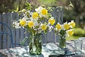 Gelb-weisse Fruehlingsstraeusse aus Narcissus (Narzissen) und Zweigen