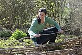 Frau flicht Beeteinfassung aus Zweigen