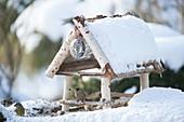 Verschneites Vogelfutterhaus mit Dompfaff und Grünfink