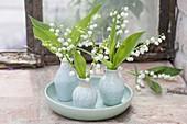 Blüten von Convallaria (Maiglöckchen) in kleinen Porzellanvasen