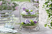Etagere mit Koerben und Herz-Motiv gefüllt mit Blüten von Syringa