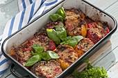 Gefüllte Paprika aus dem Ofen, dekoriert mit Basilikum
