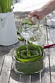 Tischgesteck aus Maisblaettern in Glasschale