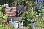 Wasserfass und Wasserhahn für die Bewässerung im Bauerngarten