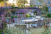 LE Haut, Guernsey: VIEW ACROSS Patio with LAVENDER, WOODEN TABLE AND CHAIRS