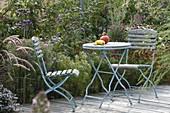 Kleine Sitzgruppe am Terrassenbeet mit Pennisetum (Federborstengras)