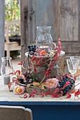 Natuerliche Tischdeko mit Weintrauben (Vitis vinifera), Rosa (Rosen)