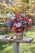 Herbststrauss mit Stauden und Früchten in Korbvase